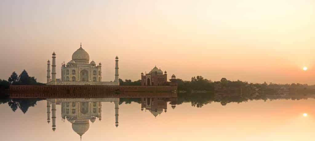 Vista del Taj Mahal a la puesta del sol reflejándose en el agua