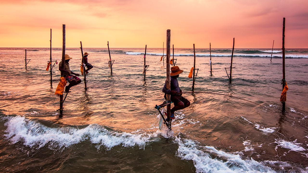 Stilt fishermen a la puesta del sol