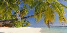 mujer sentada sobre palmera, Sun Aqua Vilu Reef